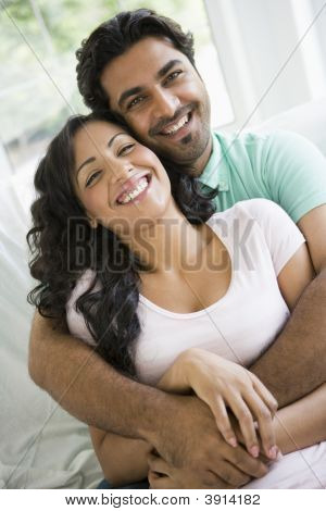 Middle Eastern Couple Sat At Home Of Sofa