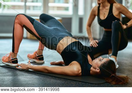 Staying Fit. Young Caucasian Woman In Sportswear Lying On Yoga Mat At Gym And Doing Abs Exercises Wi