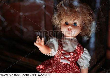 Old Doll With Scary Look In Red Dress With Blue Eyes And With Spider Web In Front Of Her. Halloween