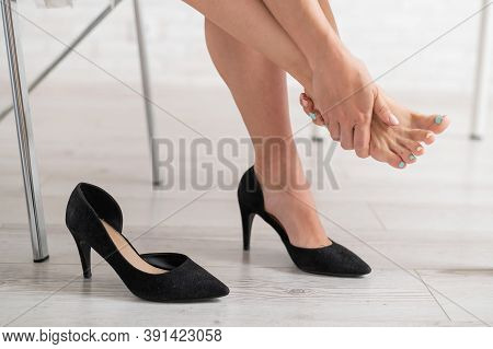 Business Woman Took Off Her Black High-heeled Shoes And Massages Her Feet. Ankle Pain From Uncomfort