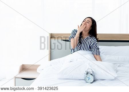 Pretty Asian Woman  Sitting On A Clean White Bed, She Covered Her Mouth And Yawning After She Woke U