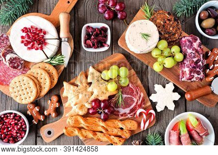 Christmas Theme Charcuterie Table Scene Against A Dark Wood Background. Assortment Of Cheese And Mea