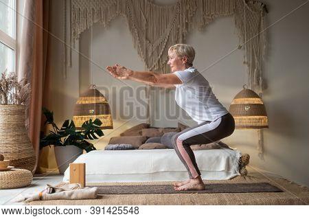Senior Woman Practicing Advanced Yoga Chair Pose Utkatasana