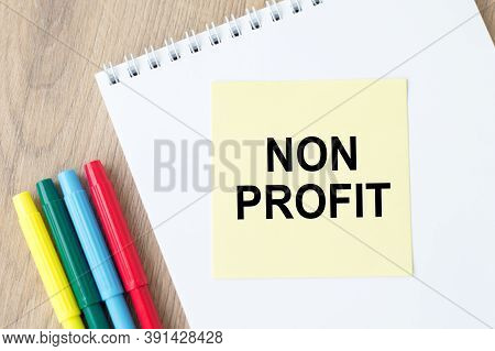 Non Profit Text On Yellow Note Paper That Lies On An Open Block On The Table Next To The Markers.