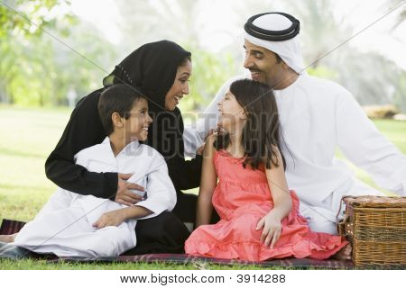 Middle Eastern Family Sat On Picnic Blanket In Park