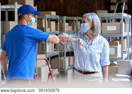 Female Warehouse Worker Manager Wearing Face Mask Greeting Male Courier Deliverer Giving Elbow Bump