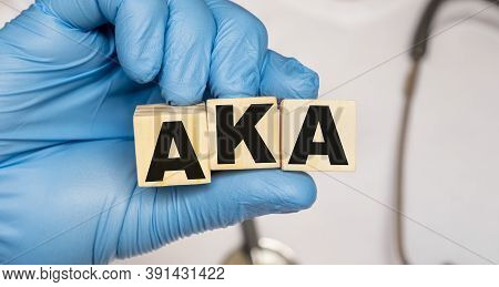 Aka Above The Knee Amputation. - Word From Wooden Blocks With Letters Holding By A Doctors Hands In