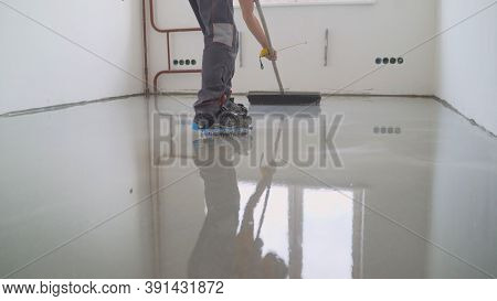 Master With A Needle Roller. Filling The Floor. A Contractor Painter Will Paint The Garage Floor To
