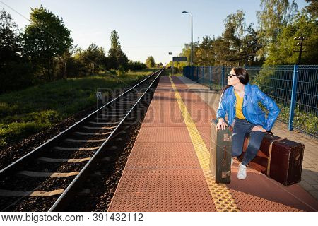 The Girl Is Sitting On The Platform Of A Railway Station. Old Travel Suitcases. Boredom And Fatigue
