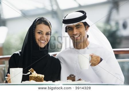 Middle Eastern Couple Eating And Drinking In Shopping Mall