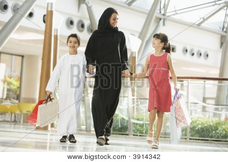 Middle Eastern Woman And Children Walking Through Shopping Mall With Bags