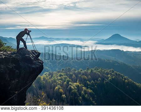 Silhouette Of Photographer In Mountain.  Nature Photographer Traveler Taking Photo Of Beautiful Morn