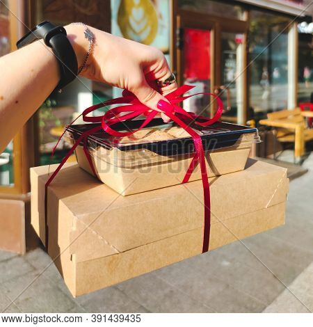 Woman's Hand Hold A Gift Red Bow Boxes With Sweets, Cookies And Cakes Photo