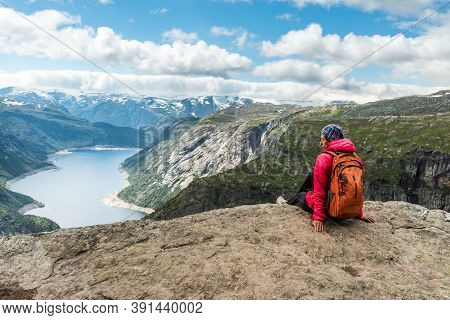 Sporty Woman Posing On Trolltunga. Happy Hiker Enjoy Beautiful Lake And Good Weather In Norway.