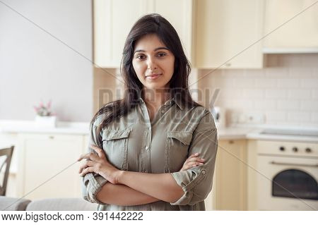 Smiling Young Pretty Indian Ethnicity Woman Looking At Camera Alone At Home In Kitchen. Confident Be