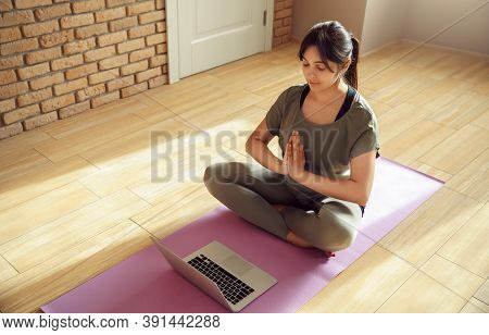 Young Healthy Calm Indian Woman Wear Sportswear Meditate Eyes Closed Watch Online Class Tutorial On