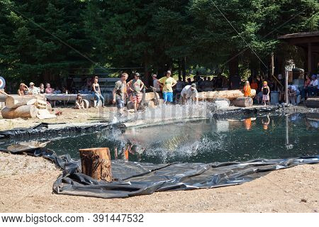 Prospect, Oregon / Usa - August 16, 2014: Volunteers Roll A Log Into A Pond With A Splash For A Skil