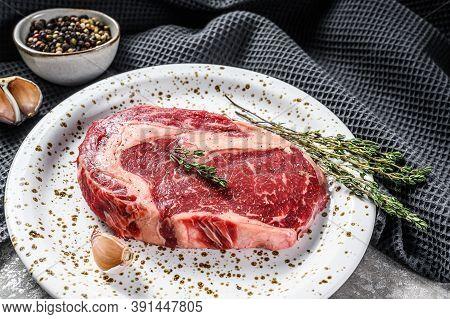 Raw Fresh Meat Ribeye Steak With Seasoning On Cutting Board. Rib Eye Beef Steak. Gray Background. To