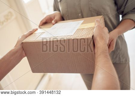Female Customer Receiving Courier Service Delivery Holding Parcel Box In Hands Standing At Home. Del