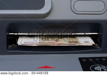 Russian Rubles Sticking Out Of An Atm Close-up. Cash Withdrawal Through An Atm, Withdrawal Of Money