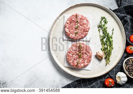 Raw Pork Patty, Ground Meat Cutlets On A Cutting Board. Organic Mince. Gray Background. Top View. Co