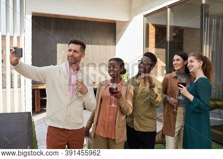 Waist Up Portrait Of Multi-ethnic Group Of Friends Taking Selfie Photo While Enjoying Party Standing