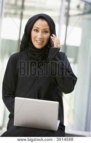 Middle Eastern Business Woman On Laptop And Cell Phone