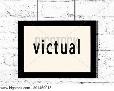 Black Wooden Frame With Inscription Victual Hanging On White Brick Wall