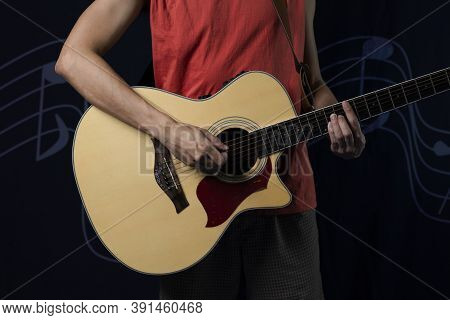Musician With An Acoustic Guitar In The Dark.