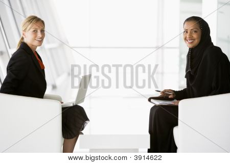 Middle Eastern And Western Women Discussing Business