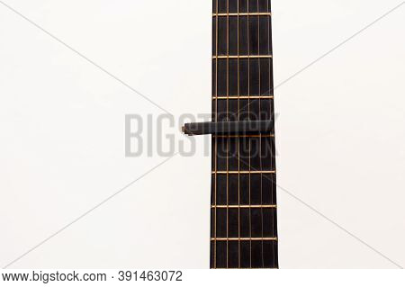 Cap On Guitar Fretboard On White Background. Close Plan. Wooden Guitar.