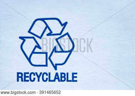 Close Up To A Recyclable Symbol On A White Cardboard.