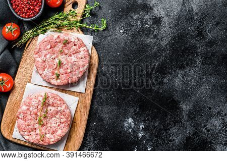 Raw Pork Cutlets, Ground Meat Patty On A Cutting Board. Organic Mince. Black Background. Top View. C