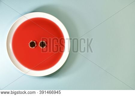 Two Eyes Of Mould Fungus, On A Plate Of Fruit Tea. Left On A Mint Colored Background.