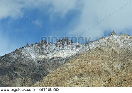 Rock Formations On A Mountain Peak Jut Into A Blue Sky With Faint Clouds. The Slopes Of The Mountain