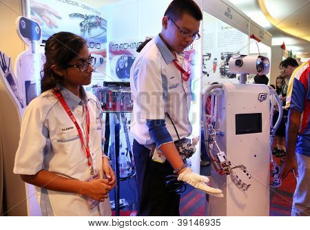 SUBANG JAYA - NOV 10: An unidentified student from Malaysia shows the robot hand mimics his fingers movement at the World Robot Olympaid on Nov 10, 2012 in Subang Jaya, Malaysia.