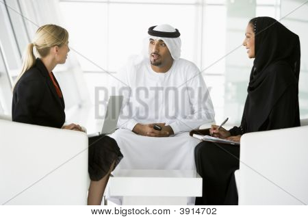 Middle Eastern And Western People Discussing Business