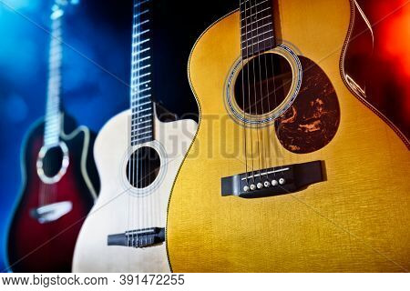 Three acoustic guitars on stage or in recording studio  background