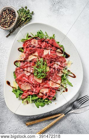 Italian Beef Carpaccio With Arugula Salad, Parmesan Cheese. Gray Background. Top View