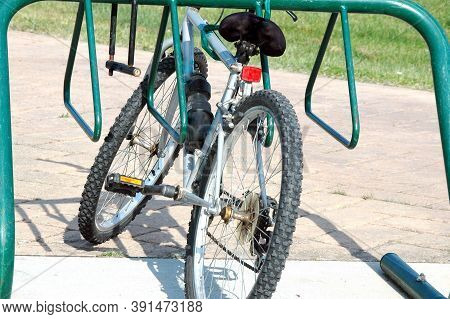 Bicycle Parked In A Green Bike Rack Outdoors.