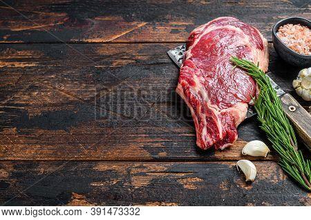 Ribeye Steak On A Meat Cleaver. Raw Marble Beef Black Angus, Rib Eye. Dark Wooden Background. Top Vi