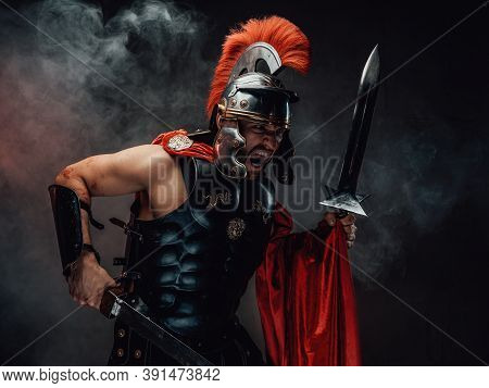 Brutal And Savage Roman Soldier In Dark Armour With Helmet And Red Cloak Screams And Assaults Holdin