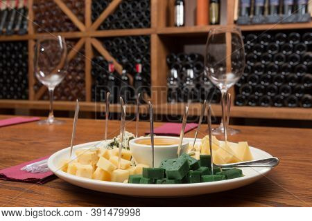 Plate With Appetizers For Wine, Several Varieties Of Cheese And Honey, On The Background Of Shelving