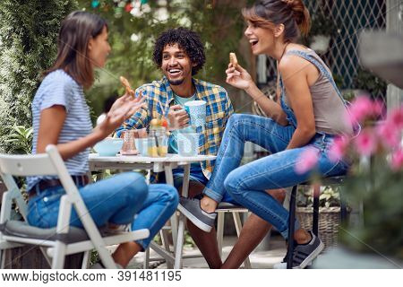 Cheerful friends enjoying snack at the bar's backyard on a beautiful weather. Quality friendship time together