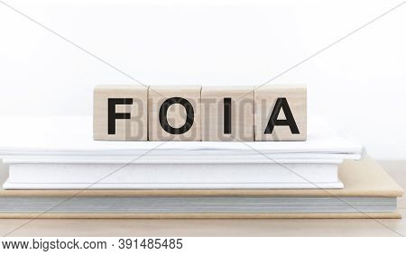 Word Foia. Wooden Cubes With Letters On A Stack Of Books, Isolated On Light Background With Copy Spa