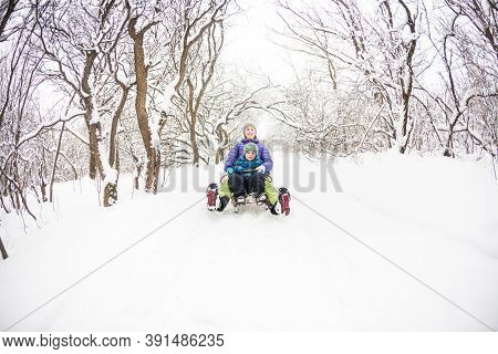 Mother With A Child Riding On A Sled. A Woman With Her Son Rides Down The Hill In A Sleigh. The Boy