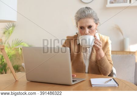 Happy Middle Aged Woman With Laptop Computer Drinking Coffee At Home.