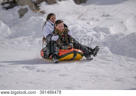 Two Happy Delightful Kids Boy And Girl In Ski Suit Riding Down Snow Hill With Pleasure On Rubber Tub