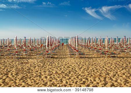 Withdrawn Umbrellas And Sunlongers On The Sandy Beach