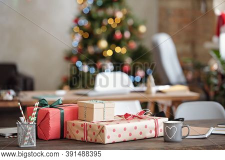 Stack of packed Christmas gifts wrapped into paper and bound with ribbons among office supplies on table against xmas tree